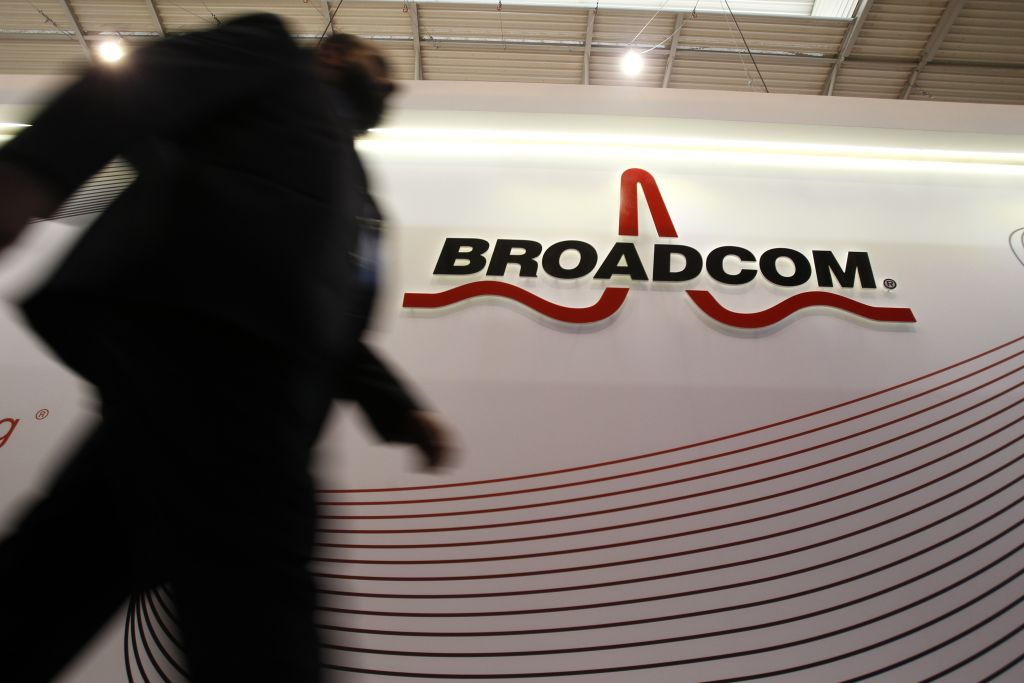 An attendee passes the Broadcom Corp. pavilon on day two of the Mobile World Congress in Barcelona, Spain, on Tuesday, Feb. 25, 2014. Top telecommunication managers will rub shoulders in Barcelona this week at the Mobile World Congress, Monday, Feb. 24 - 27, a traditional venue for showcasing the latest products for dealmaking. Photographer: Angel Navarette/Bloomberg via Getty Images